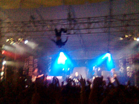 Kody Nielson hangs upside down over the stage during a performance at Auckland University of Technology
